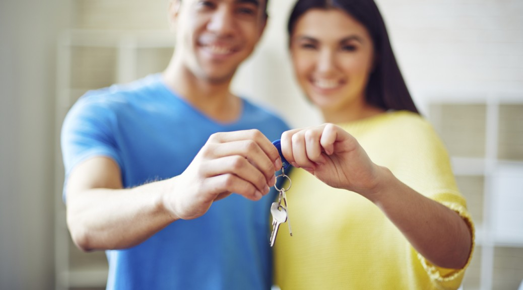 Young couple showing key from their new residence